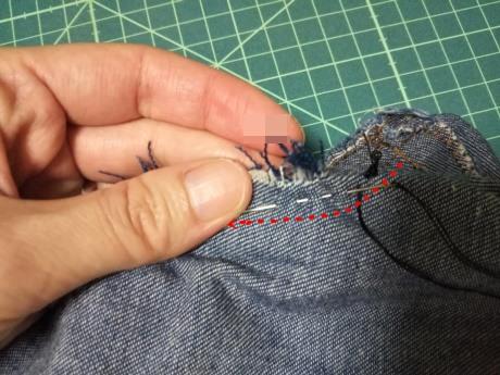 ズボンの破れを手縫いで直している写真